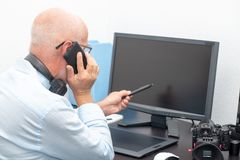 Mature photographer in his office phone. A mature photographer in his office phone Royalty Free Stock Images