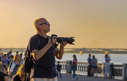 Mature photographer looking out people to shoot on Dnepr river embankment. DNEPR, UKRAINE - SEPTEMBER 10, 2016:Mature photographer looking out people to shoot on stock photo