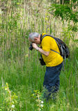 Mature photographer taking a photo. Of butterfly Royalty Free Stock Photography