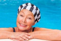 Mature in pool. Female senior workout smiling camera Royalty Free Stock Photo