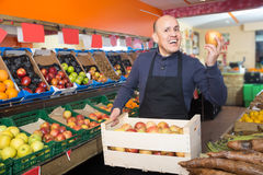 Mature positive male vendor in grocery store Royalty Free Stock Photography