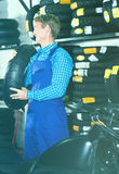 Mature positive mechanic holding new tyre for motorcycle. In workshop Stock Photography