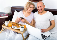 Mature positive smiling couple reading news from notebook Royalty Free Stock Photos