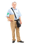 Mature postman delivering a box. Full length of a mature postman delivering a box on white background stock photos