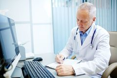 Practitioner at work. Mature practitioner making notes or prescriptions in medical form by his workplace Stock Photography