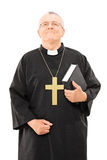 Mature priest holding a bible and looking up Stock Photos