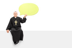 Mature priest holding a speech bubble seated on panel Stock Images