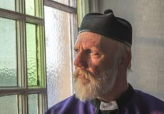Mature priest looking out of a church window. With a thoughtful expression royalty free stock image