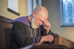 Mature priest looking worried, praying in a church. Mature priest looking upset and worried, praying in a church royalty free stock photo