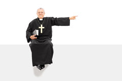 Mature priest pointing with his hand seated on panel royalty free stock image