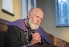 Mature Priest praying in a church. Setting royalty free stock photography