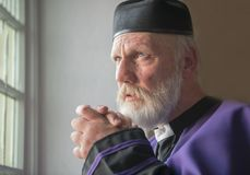 Mature priest praying in a church. With a thoughtful expression stock photo