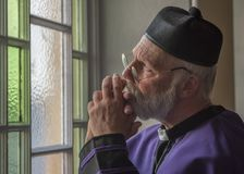 Mature Priest praying, looking out through a window. Mature Priest praying, looking out through a Church window stock photo