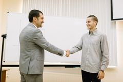 Mature businessman shaking hands with a student on a blurred background. Small business concept. royalty free stock images