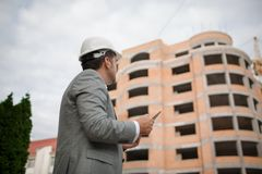 A foreman looking at the new modern building on an industrial background. Building technologies concept. Copy space. A mature, professional foreman in a hard Royalty Free Stock Photo