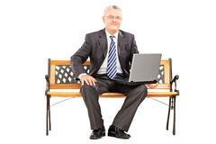 Mature professional man sitting on a wooden bench and working on Stock Photography