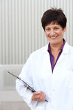 Mature professional woman dressed in labcoat. Smiling mature professional woman dressed in labcoat standing outside Royalty Free Stock Image