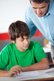 Mature Professor Assisting Teenage Boy At Desk Royalty Free Stock Image