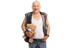Mature punk rocker holding a teddy bear Royalty Free Stock Image
