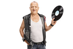 Mature punk rocker holding a vinyl. Record and looking at the camera isolated on white background Royalty Free Stock Images