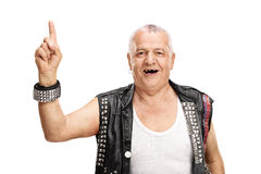 Mature punk rocker pointing up with finger. Mature punk rocker pointing up with his finger and looking at the camera isolated on white background Royalty Free Stock Photo