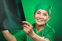 Mature radiologist. Close-up portrait of a mature radiologist examining an xray roentgenogram over a green background Royalty Free Stock Photos