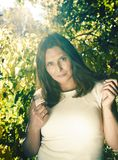 Mature real brunette woman in green spring park, lifestyle concept outside. Sunlight everywere royalty free stock image