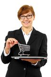 Mature red haired business woman with shopping cart, laptop Royalty Free Stock Photos