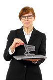 Mature red haired business woman with shopping cart, laptop Stock Photo
