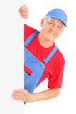 Mature repairman smiling and posing behind a blank panel Stock Photos