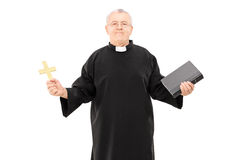 Mature reverend in black mantle holding bible and a cross. Isolated on white background Stock Images