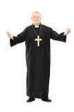 Mature reverend in black mantle with open hands. Full length portrait of mature reverend in black mantle with open hands isolated on white background Royalty Free Stock Photography