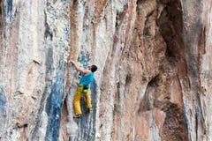 Mature Rock Climber ascending steep colorful rocky Wall Lead Climbing Stock Photos