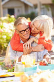 Mature Romantic Couple Enjoying Outdoor Meal In Garden Stock Images