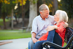 Mature Romantic Couple Sitting On Park Bench Together Royalty Free Stock Photography