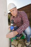 Mature roofer applying weld into gutter parts Stock Images