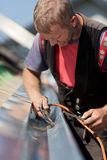 Mature roofer applying weld into the gutter Stock Photography