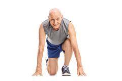 Mature runner in starting position preparing to run Royalty Free Stock Images