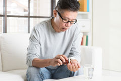 Mature 50s Asian Chinese man eating medicine Stock Photo