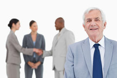 Mature salesman with trading partners behind him Royalty Free Stock Photography