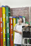 Mature salesperson standing by multicolored ladders in hardware store Stock Photo