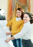 Mature saleswoman helps girl chooses white bridal gown Stock Photos