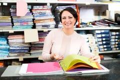 Mature saleswoman offers various fabrics types Stock Photos