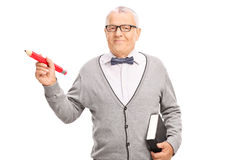 Mature school teacher holding a big red pencil Royalty Free Stock Image