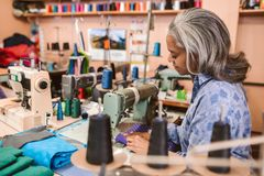 Mature woman sitting in her workshop using a sewing machine royalty free stock photos