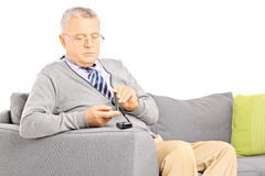 Mature seated on a sofa measuring sugar level in blood using glu Stock Photography