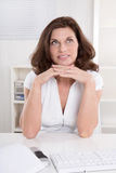 Mature secretary is pondering at office. Stock Image