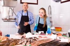Mature seller and assistant offering fresh fish Royalty Free Stock Photo