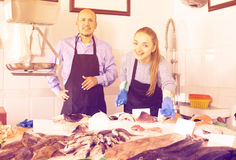 Mature seller and assistant offering fresh fish Royalty Free Stock Photos