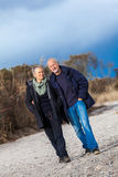 Mature senior couple walking on the beach autumn winter Royalty Free Stock Photo